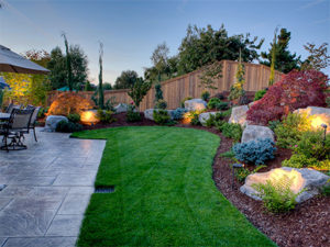 Residential Landscaping Featuring Stained and Stamped Concrete Patio, Outdoor Lighting and Fence