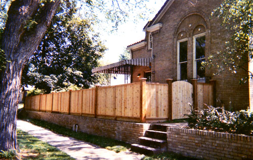 Capped Privacy Fence with Bulky Posts Curved Top Gate and Brick Retaining Wall